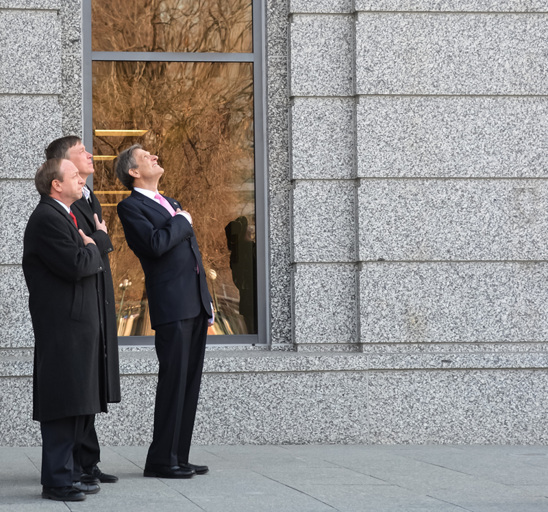 From left to right, Attorney General John Suthers, Governor John Hickenlooper and Chief Justice Michael L. Bender watch on Jan. 14, 2013, as the American and Colorado flags are raised for the first time at the Ralph L. Carr Colorado Judicial Center.